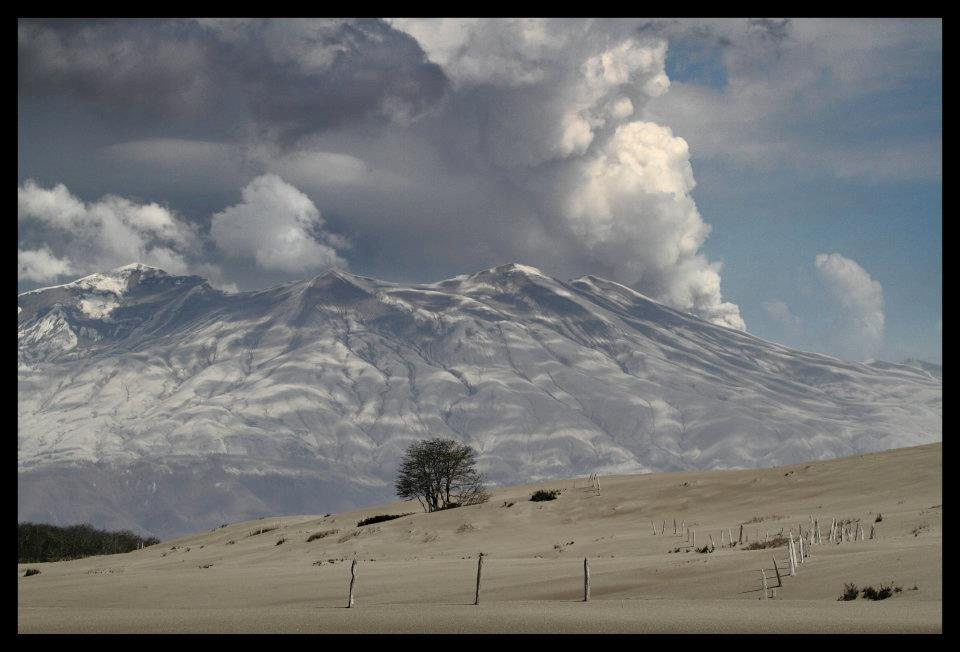 photo of a volcano with smoke billowing from its top
