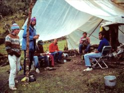 a group of researchers sitting around a campsite